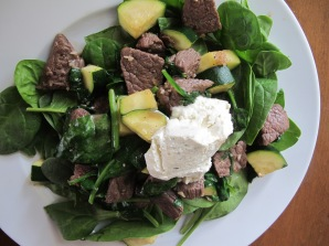 Steak and spinach salad, topped with Boursin cheese